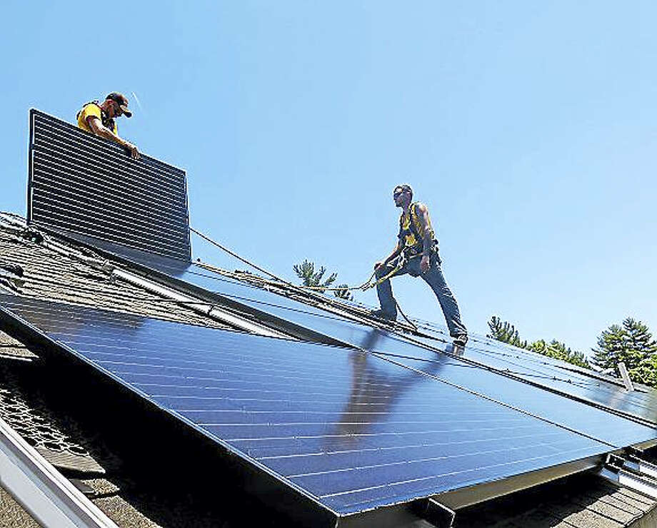Contributed photo Solar energy installers place panels on a home in Barkhamsted, where 14 homeowners signed up for the alternative energy source during the 18-week Solarize Barkhamsted. Photo: Journal Register Co.