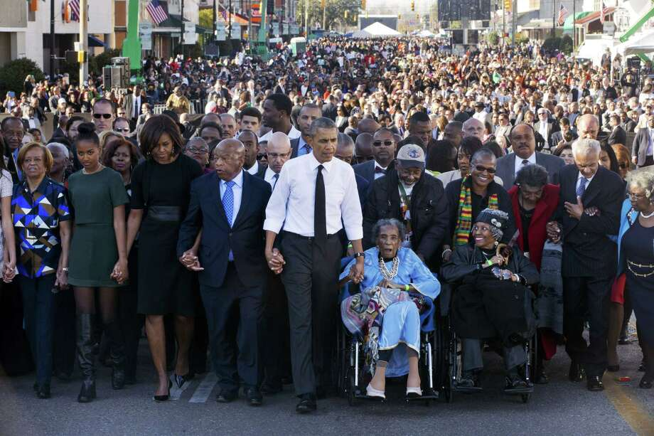 "President Barack Obama, center, walks as he holds hands with Amelia Boynton, who was beaten during ""Bloody Sunday,"" as they and the first family and others including Rep. John Lewis, D-Ga,, left of Obama, walk across the Edmund Pettus Bridge in Selma, Ala. for the 50th anniversary of ""Bloody Sunday,"" a landmark event of the civil rights movement Saturday. From front left are Marian Robinson, Sasha Obama and first lady Michelle Obama. Photo: Associated Press  / AP"