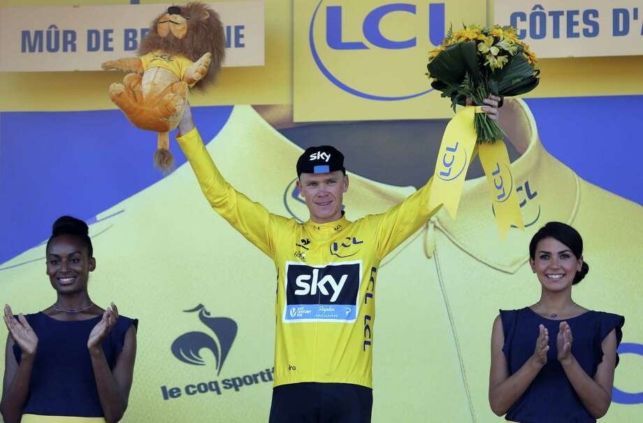 Christopher Froome, wearing the overall leader's yellow jersey, celebrates on the podium of the eighth stage of the Tour de France on Saturday. Photo: Christophe Ena — The Associated Press  / AP