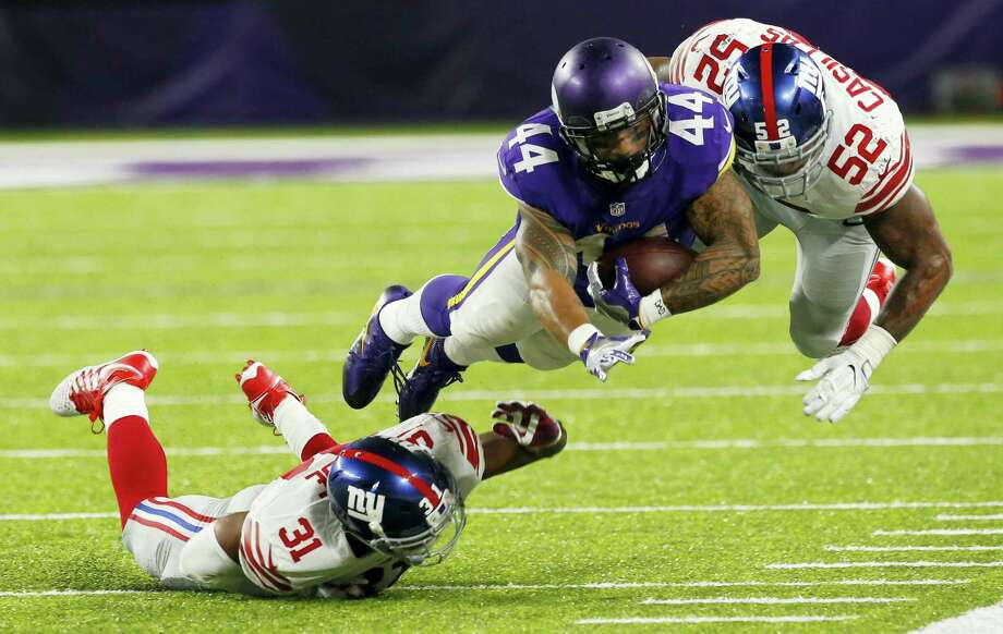 Vikings running back Matt Asiata dives for extra yardage between Giants defenders Trevin Wade, left, and Jonathan Casillas during the second half Monday. Photo: Jim Mone — The Associated Press  / Copyright 2016 The Associated Press. All rights reserved.