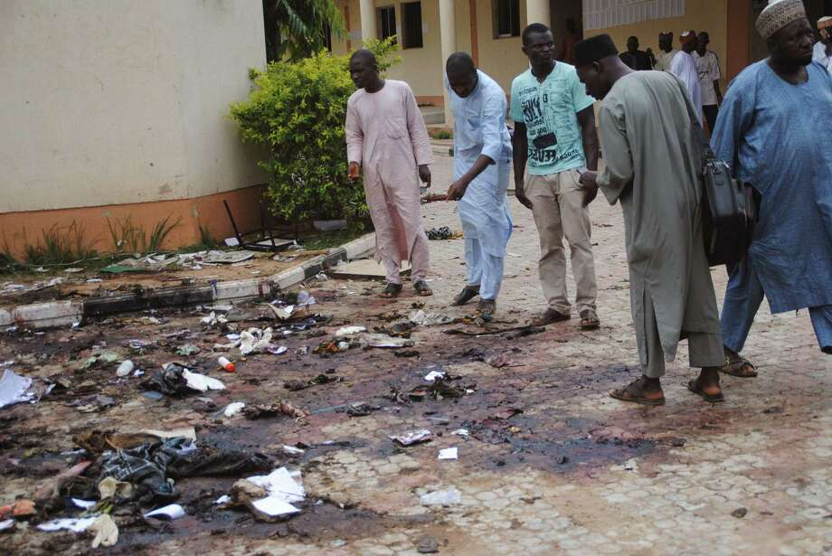 In this file photo from July 7, people look at the site of another Boko attack. A bomb blast at a university in Zaria, Nigeria, killed dozens, including a 2-year-old toddler, the Kaduna state governor reported. Photo: AP File Photo / AP
