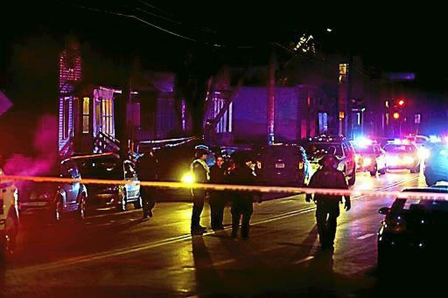 """Madison Police investigate the scene of a shooting on Williamson Street, late Friday, March 6, 2015 in Madison, Wis.  A 19-year-old black man died Friday night after being shot by an officer in Madison, authorities said. The man was shot after an altercation with the officer and died at a hospital, Police Chief Mike Koval said. He did not know if the man was armed, but said the """"initial findings at the scene did not reflect a gun or anything of that nature that would have been used by the subject.  (AP Photo/Wisconsin State Journal, Steve Apps) Photo: AP / Wisconsin State Journal"""