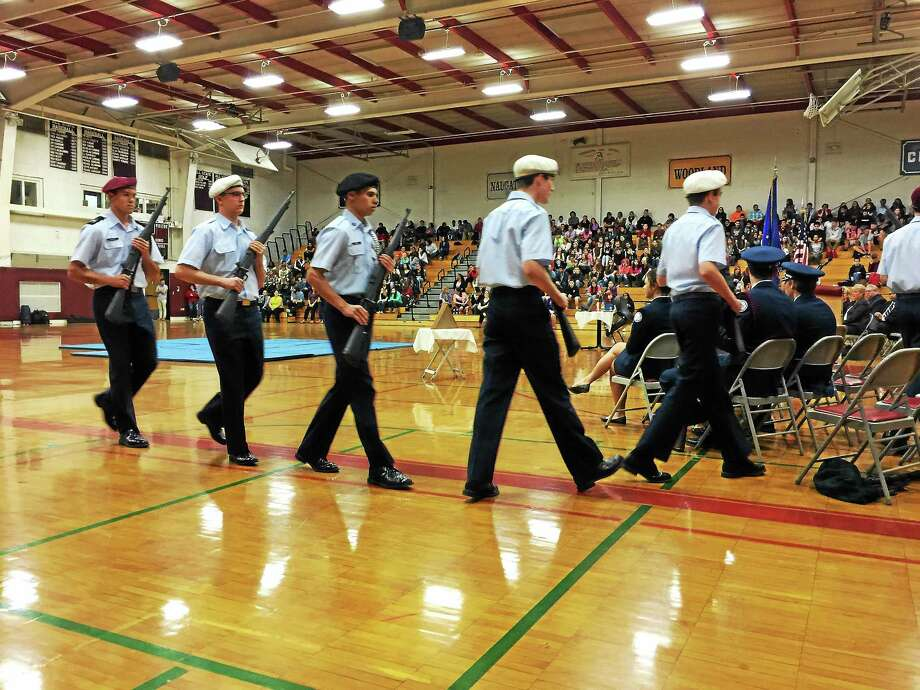 The Torrington AFJROTC trick drill team files to their seats during a ceremony held Wednesday at Torrington High School to honor veterans and mark the upcoming Veterans Day holiday. Photo: BEN LAMBERT — The Register Citizen