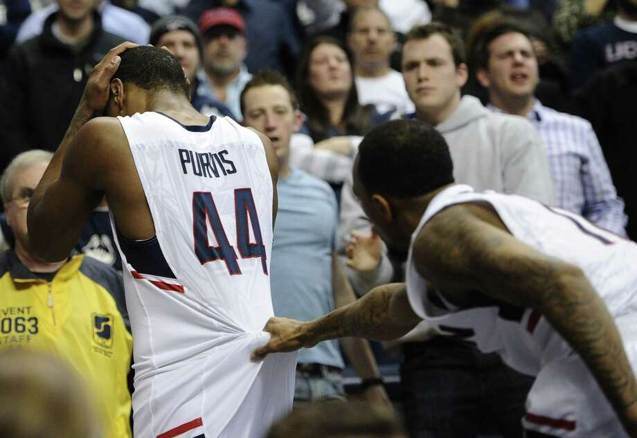 UConn's Ryan Boatright, right, grabs teammate Rodney Purvis as he walks off the court holding his head during the first half of Thursday's game against Memphis. Purvis took a hard fall on his head resulting in a flagrant foul against Memphis' Calvin Godfrey. Memphis won 54-53. Photo: Jessica Hill — The Asociated Press  / FR125654 AP