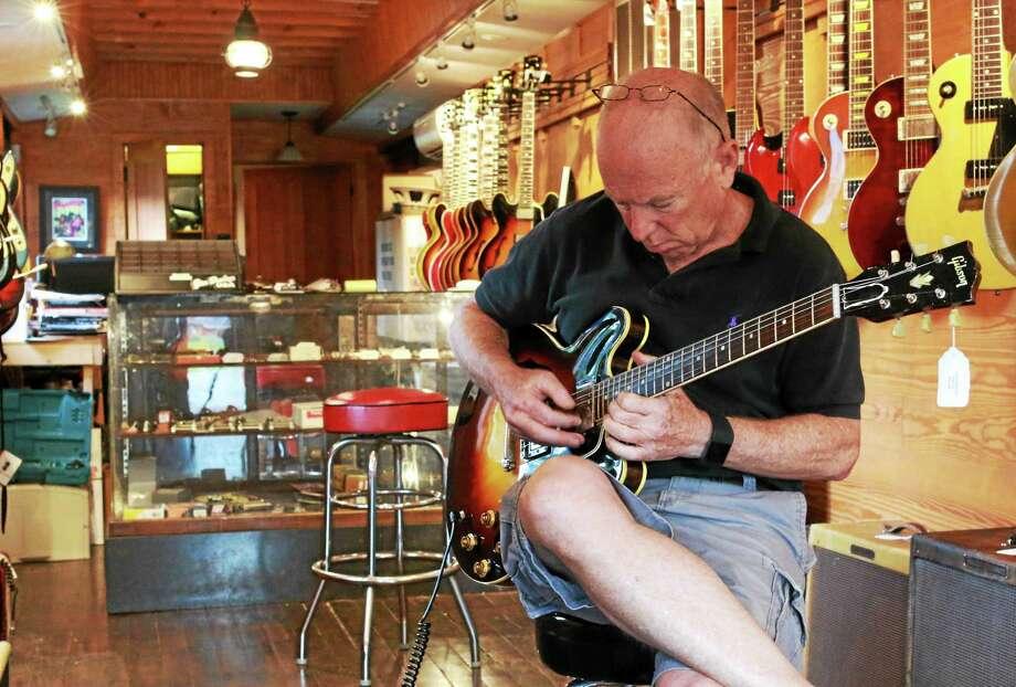 Photo by John Fitts  OK Vintage Guitars owner Charlie Gelber plays a 1959 Gibson ES-335 at OK Vintage Guitars in Kent. Photo: Journal Register Co.