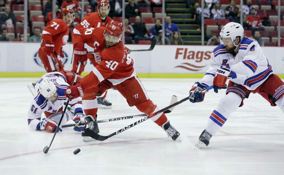 Red Wings left wing Henrik Zetterberg (40) controls the puck in front of Rangers defenseman Kevin Klein during the first period on Saturday. Photo: Carlos Osorio — The Associated Press  / AP