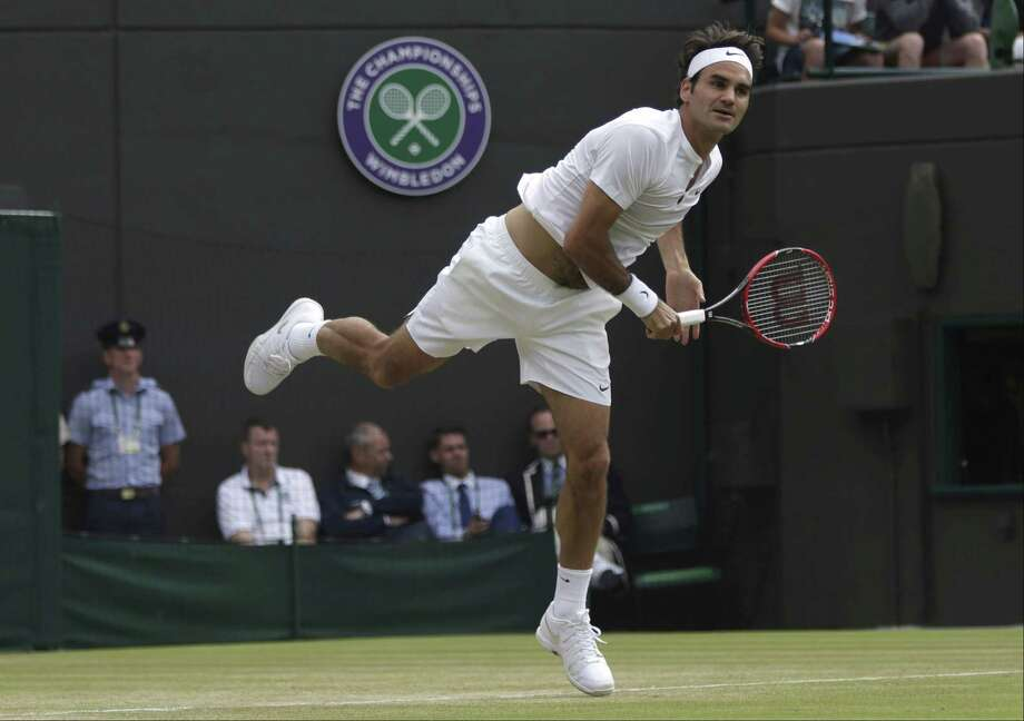 Roger Federer serves to Gilles Simon during their match Wednesday at the All England Lawn Tennis Championships in Wimbledon, London. Photo: Pavel Golovkin — The Associated Press  / AP
