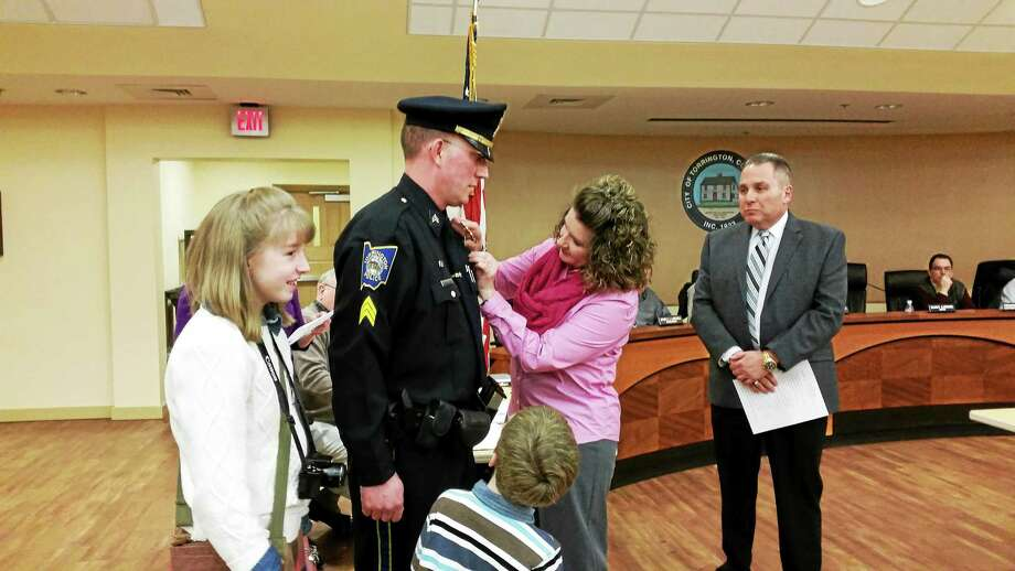 Sgt. Matthew Southard is pinned by his wife, Rebecca, during the Board of Public Safety meeting Wednesday evening. Photo: Amanda Webster — The Register Citizen