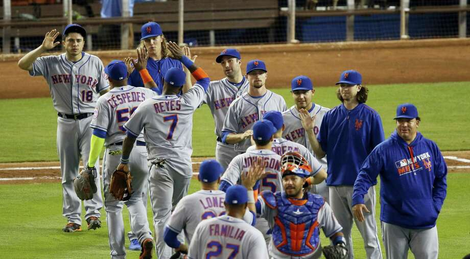 Mets players celebrate after they beat the Marlins in Miami on Sunday. Photo: Joe Skipper — The Associated Press  / FR171174 AP