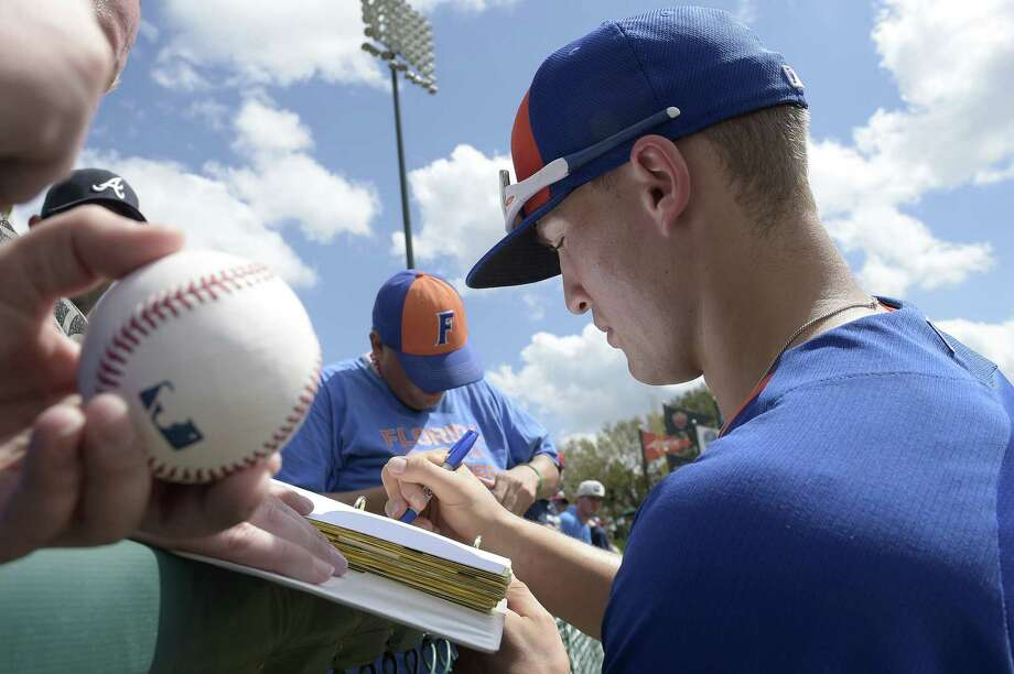 The New York Mets' Brandon Nimmo signs autographs for fans before a spring training game against the Atlanta Braves on Wednesday in Kissimmee, Fla. Photo: Phelan M. Ebenhack — The Associated Press  / FR121174 AP