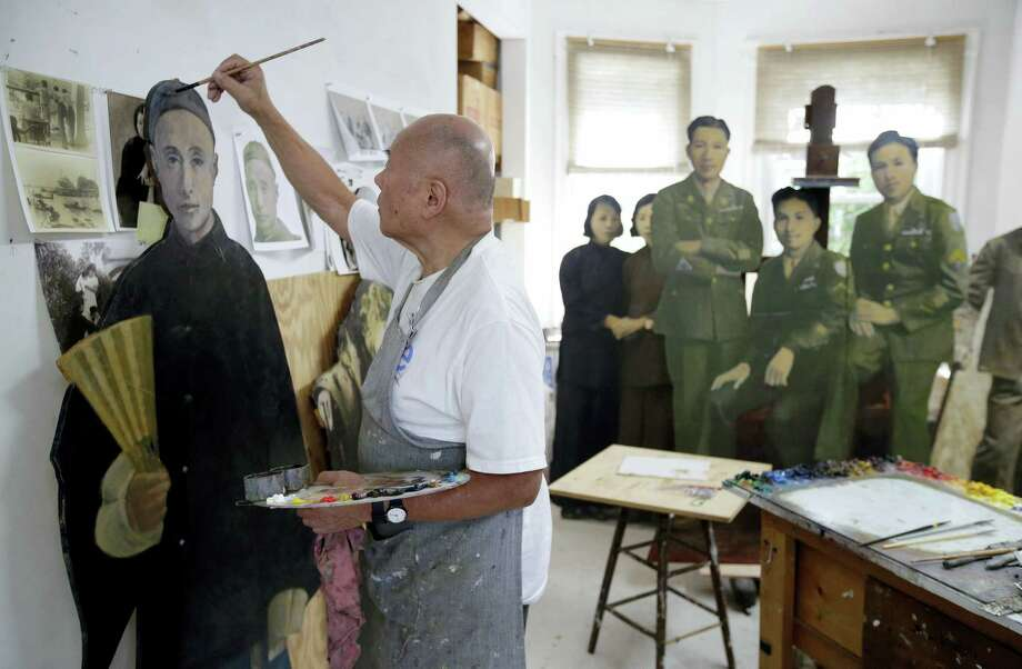 Artist Wen-ti Tsen paints life-sized portraits in his studio in Cambridge, Mass. Wen-ti Tsen, whohas been installing the portraits on the street around Boston's Chinatown neighborhood, says they're meant to underscore how the city's building boom is displacing longtime residents and businesses in the historic downtown enclave. Photo: Steven Senne — The Associated Press  / Copyright 2016 The Associated Press. All rights reserved.