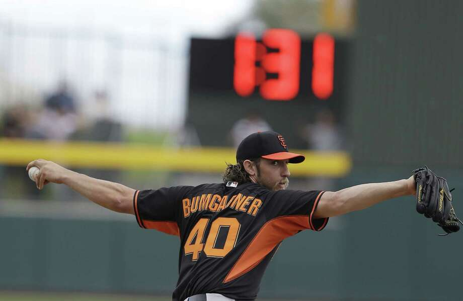 San Francisco Giants pitcher Madison Bumgarner warms up before the bottom of the second inning against the Oakland Athletics as a clock counts down time between innings Tuesday in Mesa, Ariz. Photo: Darron Cummings — The Associated Press  / AP