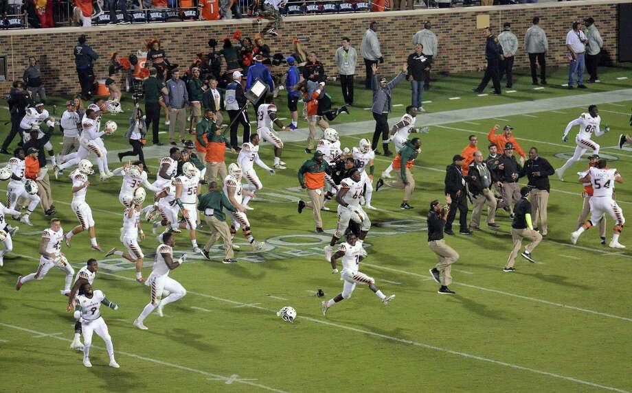 Miami players run onto the field to celebrate their 30-27 win over Duke Saturday. Photo: The Associated Press  / The Herald-Sun