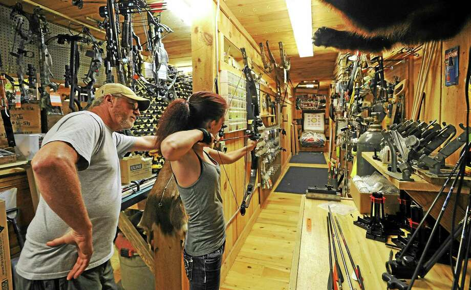 Ashton Petrones of Kent tries out a bow after it was ajusted by Newbury Archery owner Barry Hall, left. Photo: John Fitts — The Register Citizen