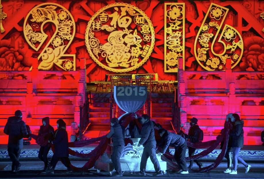 Workers push a 2016 countdown clock into position during a rehearsal for a New Year's Eve countdown celebration at the Imperial Ancestral Temple in Beijing Wednesday. At 8 hours ahead of Greenwich Mean Time, China will ring in 2016 ahead of much of the rest of the world on Thursday night. Photo: Associated Press Photo/Mark Schiefelbein  / AP