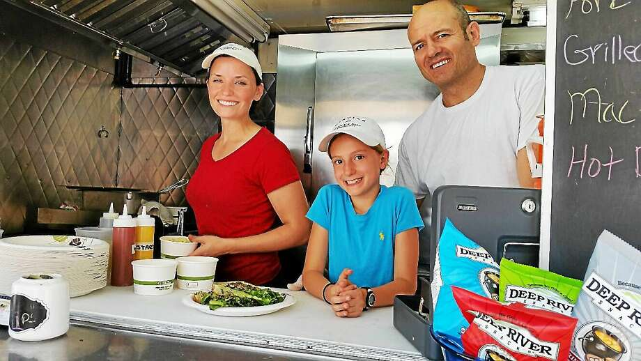 N.F. Ambery Selena Gearinger; Mary Katherine Eddy; and her father chef Chris Eddy of Morris sell plates of fresh food from The Farm Truck at the third annual Morris Marketplace. Photo: Journal Register Co.