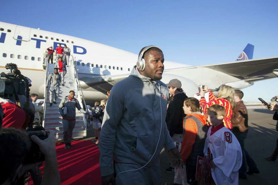 Ohio State quarterback Cardale Jones, center, and teammates disembark after arriving at an airport in Phoenix on Sunday. Photo: Cheryl Evans — The Arizona Republic  / The Arizona Republic