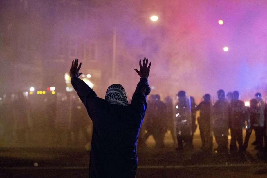A protestor faces police enforcing a curfew Tuesday, April 28, 2015, in Baltimore. A line of police behind riot shields hurled smoke grenades and fired pepper balls at dozens of protesters to enforce a citywide curfew. (AP Photo/Matt Rourke) Photo: AP / AP