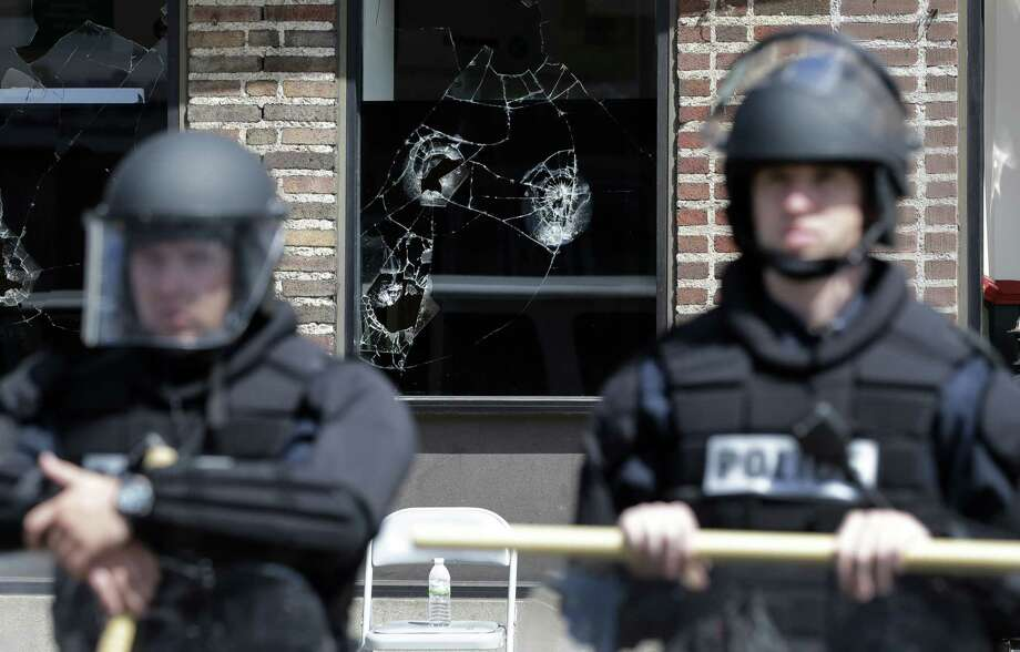 Broken store windows remain as members of the Anne Arundel County Police guard the intersection of North Avenue and Pennsylvania Avenue Wednesday in Baltimore. Schools reopened across the city and tensions seemed to ease Wednesday after Baltimore made it through the first night of its curfew without the widespread violence many had feared. People in Baltimore have been angry over the police-custody death of Freddie Gray. Photo: AP Photo  / AP