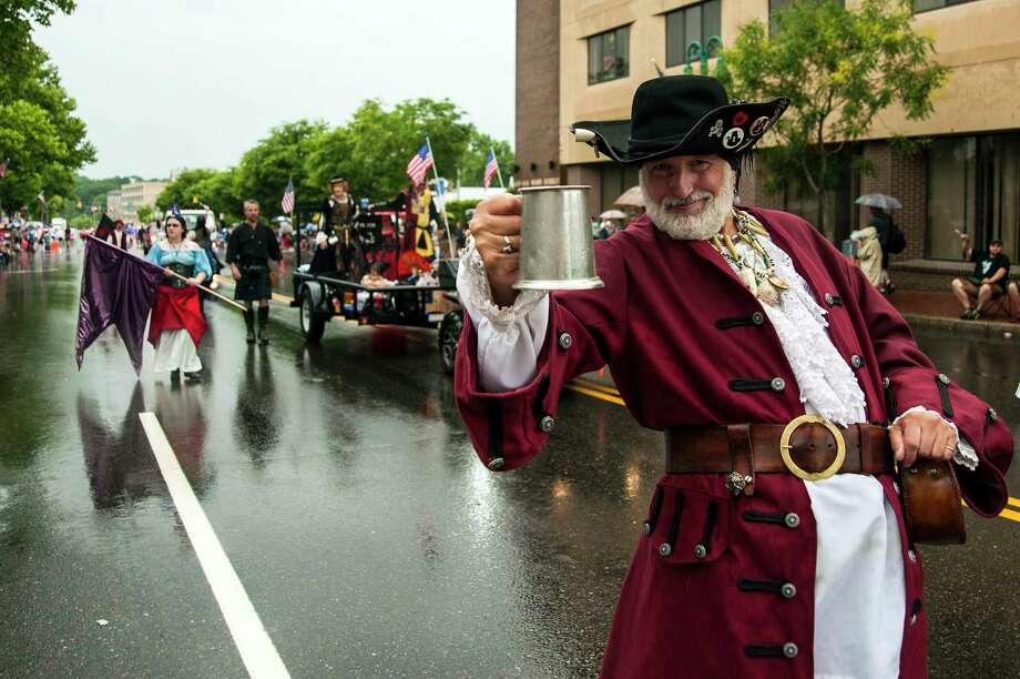 In this July 4, 2014 photo, members of the Connecticut Renaissance Faire in Norwich entertain the wet spectators at the WILI Boom Box Parade in Willimantic, Conn. Willimanticís annual Independence Day parade once again will include the traditional Little League teams, floats sponsored by local businesses, fire trucks, and politicians. But, for the 30th consecutive year, there will be no marching bands. (Daniel Owen/The Hartford Courant via AP) MANDATORY CREDIT Photo: AP / The Hartford Courant