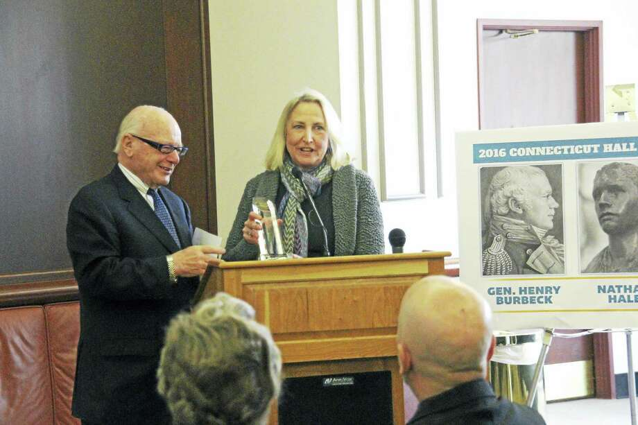 State Rep. Roberta Willis, standing in for actress and Salisbury resident Meryl Streep, accepts the induction into the Connecticut Hall of Fame at the Legislative Office Building in Hartford Monday from state Sen. Joe Crisco. Photo: Contributed Photo