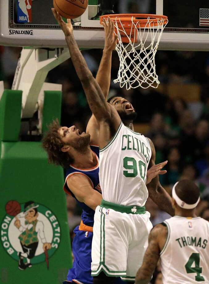 Knicks center Robin Lopez, left, vies for control of the ball with Celtics forward Amir Johnson on Sunday. Photo: Steven Senne — The Associated Press  / AP