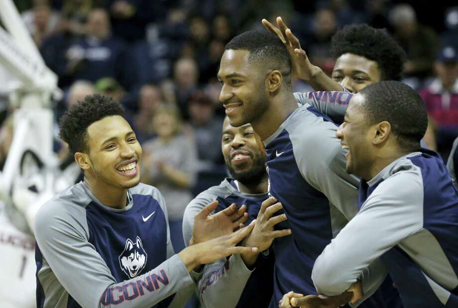 UConn's Jalen Adams (at left, front row), Sam Cassell Jr., Phillip Nolan, and Rodney Purvis, celebrate as Nolan walks on to the court during Senior Day ceremonies before the Huskies defeated UFC Sunday. Photo: Steven Senne — The Associated Press  / AP