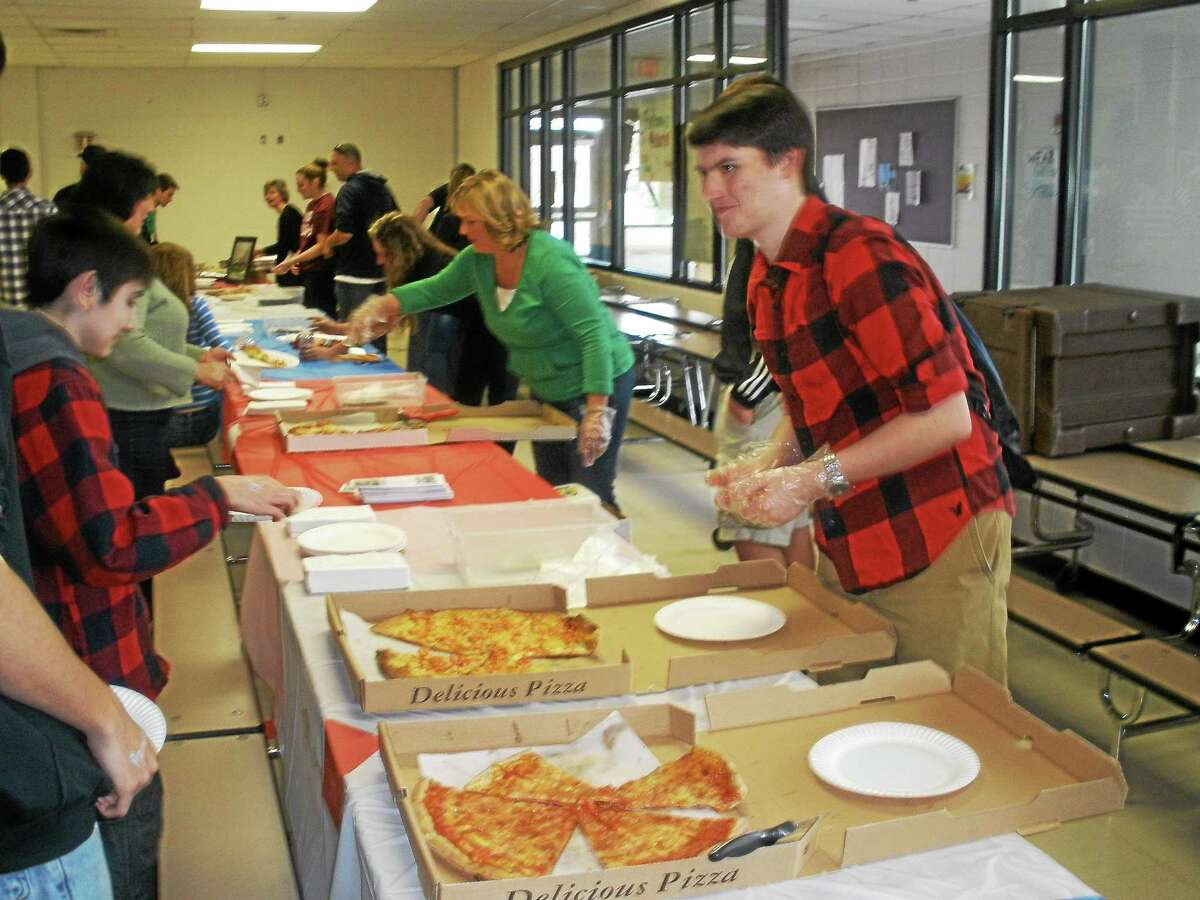 Stephen Underwood photo Matt Ahlman, a junior at THS, helps serve slices at the event.