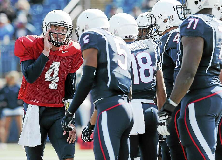 UConn quarterback Bryant Shirreffs, left, talks with his team during the first half of UConn's Blue-White spring game at Rentschler Field in April. Photo: Jessica Hill — The Associated Press FILE PHOTO  / FR125654 AP