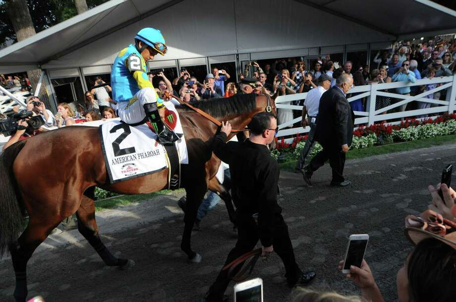 Victor Espinoza adjusts his stirrups while riding American Pharoah out of the paddock before the Travers Stakes on Saturday. Photo: The Associated Press  / Albany Times Union