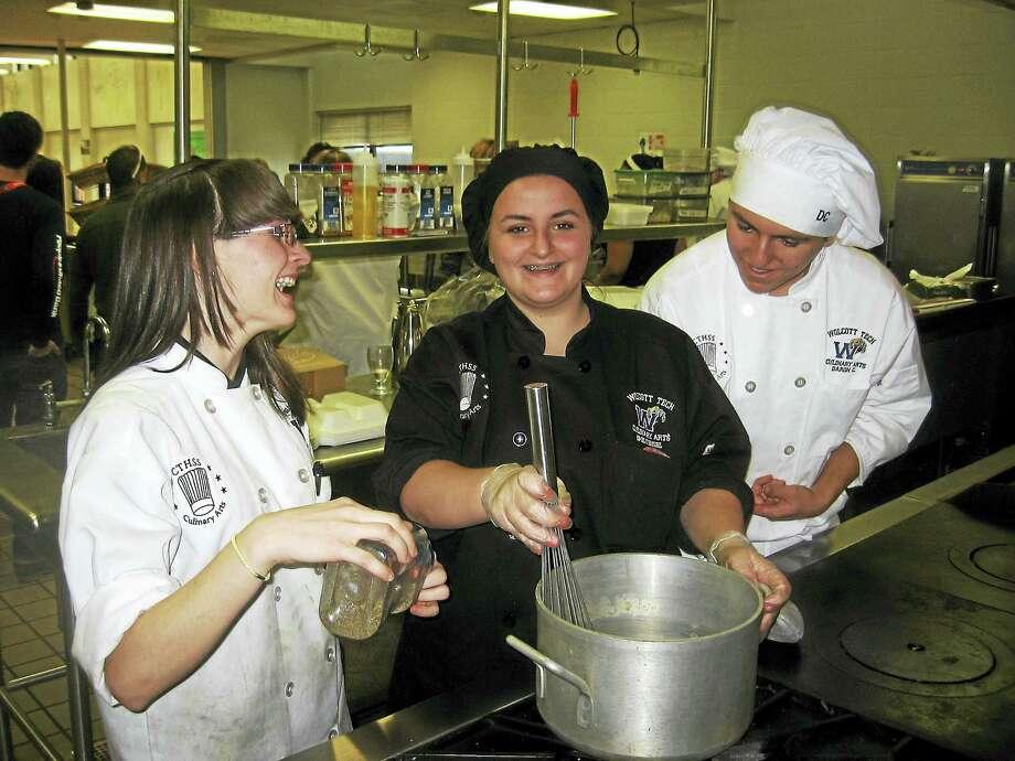 Ashley Murelli, left, Emily Engel, center, and Davon Colgan work in the kitchen at Wolcott Tech Thursday. Photo: Photo By John Torsiello