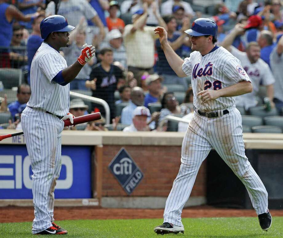 The Mets' Juan Uribe, left, greets Mets Daniel Murphy after Murphy scored the go-ahead run in the seventh inning on Sunday. Photo: Kathy Willens — The Associated Press  / AP