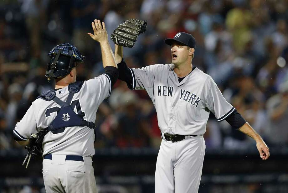 New York Yankees closer Andrew Miller and catcher Brian McCann celebrate after getting the final out of their 3-1 win over the Braves on Saturday in Atlanta. Photo: John Bazemore — The Associated Press  / AP