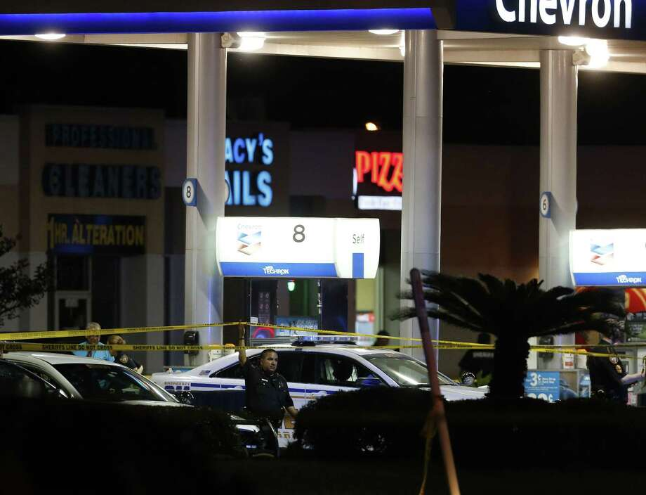 Officials investigate the scene at a gas station where a sheriff's deputy in uniform was fatally shot Friday, Aug. 28, 2015, in Houston. Harris County Sheriff's Office spokesman Ryan Sullivan said the deputy was pumping gas into his vehicle on Friday night when a man approached him from behind and fired multiple shots. Photo: Karen Warren/Houston Chronicle Via AP   / Houston Chronicle