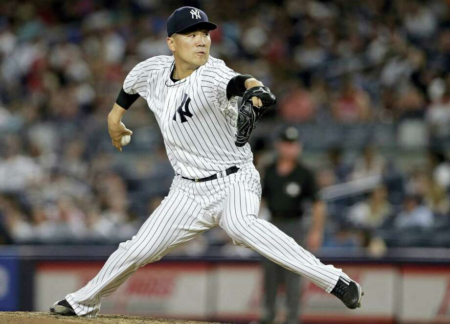 Yankees starting pitcher Masahiro Tanaka delivers a pitch during the third inning against the Red Sox on Sunday in New York. Photo: Adam Hunger — The Associated Press  / FR110666 AP