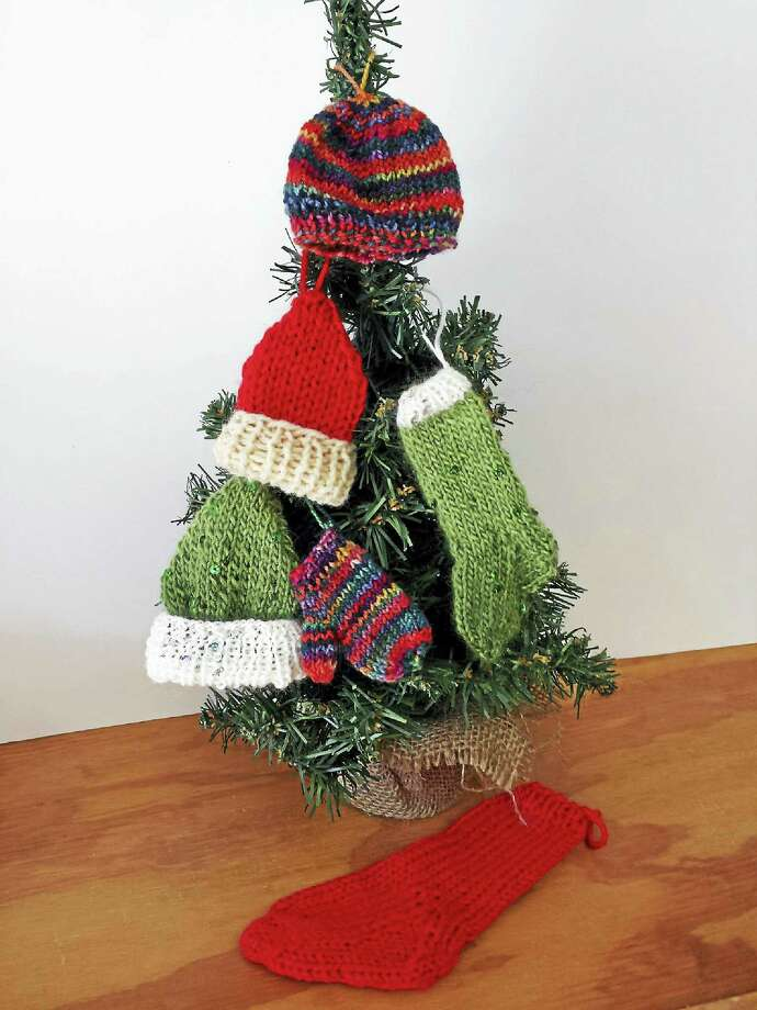 Photo by Ginger Balch A mitten tree, adorned with cozy, handmade  hats and mittens. Pick up a free kit from In Sheep's Clothing on Small Business Saturday, and knit these adorable miniature ornaments yourself. Photo: Digital First Media