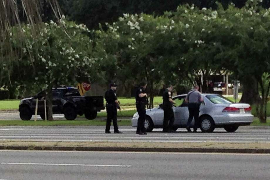 Authorities talk to the driver of a car near an area where several officers were shot while on duty less than a mile from police headquarters on Sunday, July 17, 2016 in Baton Rouge, La. Photo: AP Photo/Mike Kunzelman  / AP