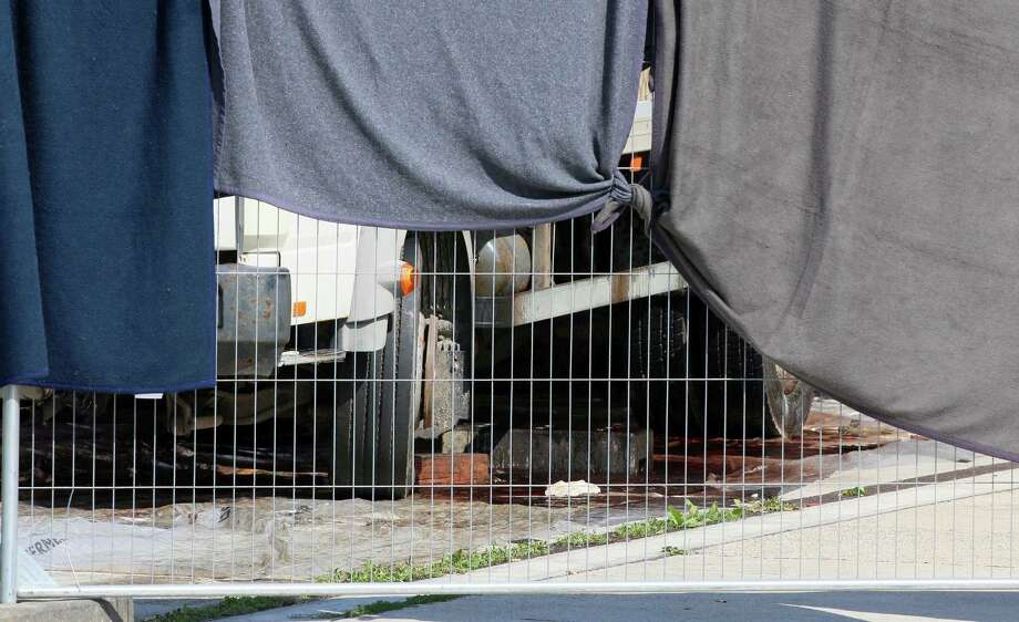 Blankets cover the view on the bottom part of a truck that is investigated at a veterinary border station at the Austrian/Hungarian border in Nickelsdorf, Austria, Friday, Aug 28, 2015. The truck was found parked on a main Austrian highway on Thursday with 71 migrants suffocated to death. Photo: AP Photo/Ronald Zak   / AP