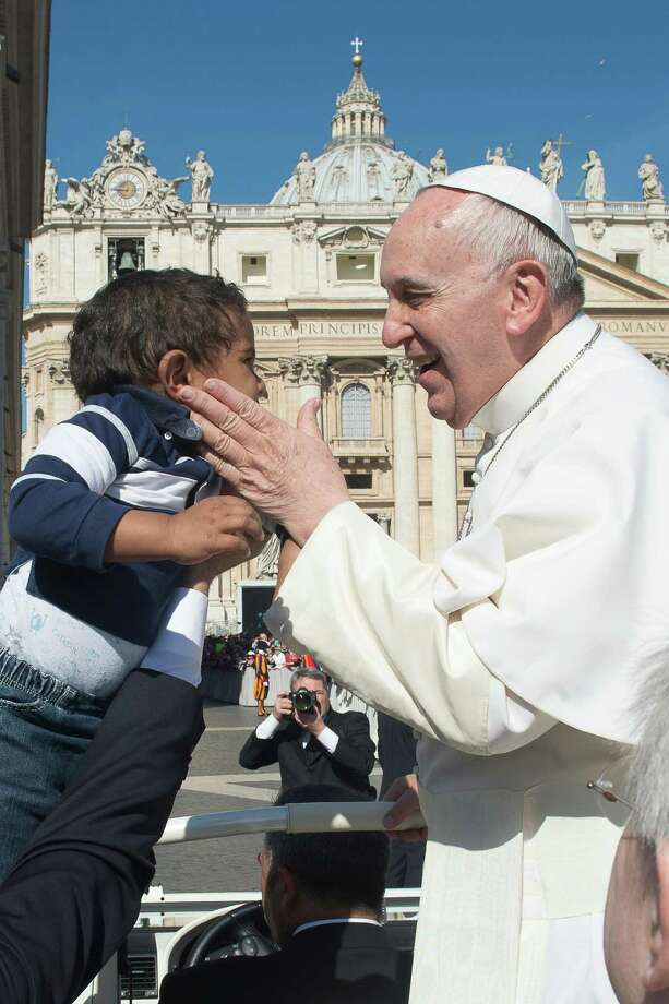 Pope Francis caresses a child as he arrives for his weekly general audience, in St. Peter's Square, at the Vatican, Wednesday, April 22, 2015. (LíOsservatore Romano/Pool Photo via AP) Photo: AP / L'Osservatore Romano Pool