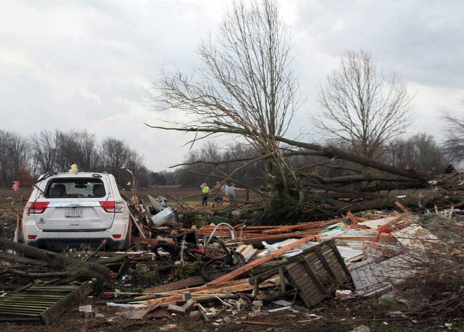 "Neighbors inspect the remains of a storm-damaged home in the Roundaway community near Clarksdale, Miss., Wednesday, Dec. 23, 2015. A storm system forecasters called ""particularly dangerous"" killed multiple people as it swept across the country Wednesday. Photo: Troy Catchings/The Press Register Via AP / The Press Register"