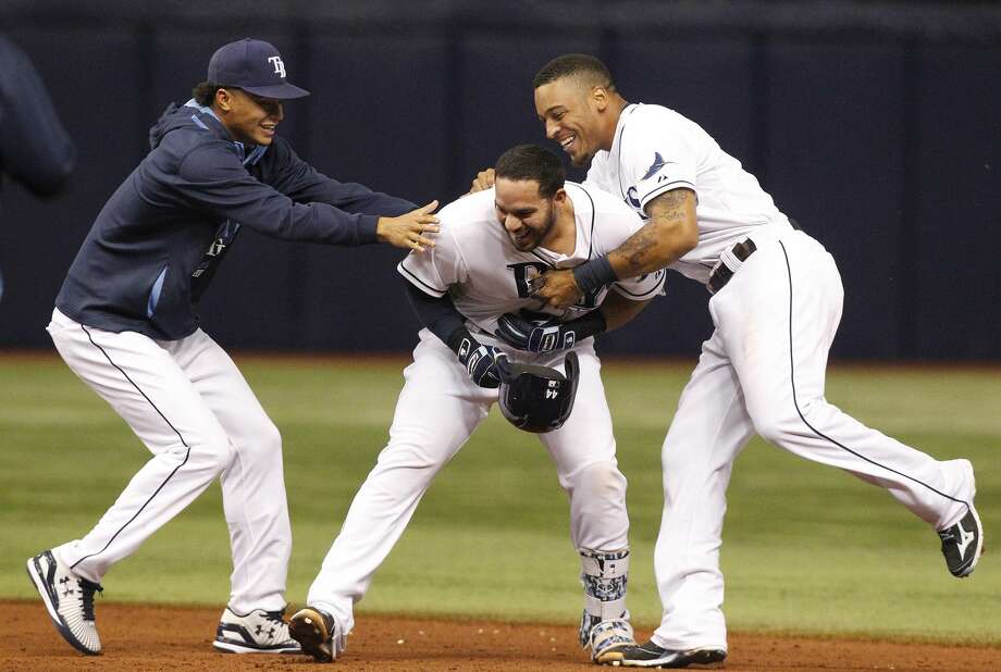 Tampa Bay Rays pitcher Chris Archer, left, and Desmond Jennings, right, jump on Rene Rivera, center, after Rivera's walk-off single in the ninth inning of Thursday's game in St. Petersburg, Fla. Photo: James Borchuck — The Tampa Bay Times  / Tampa Bay Times