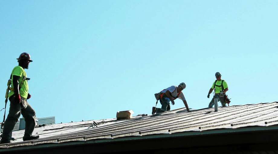 Lamont Foy, Kevin Morin and Pete Willette of Beailieu work on the roof of Barkhamsted Elementary School. Photo: John Fitts – The Register Citizen