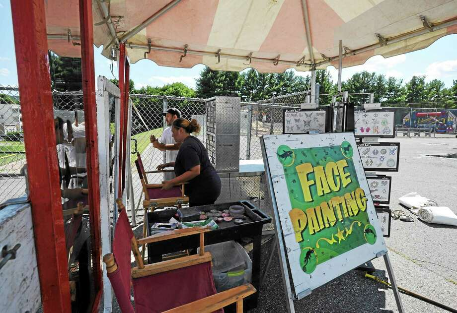 Sherry Deziel and Hector Maldonado work on setting up the face painting and body art booth for Fuse Fest. They were working for vendor R.W. Commerford and Sons. Photo: John Fitts — The Register Citizen