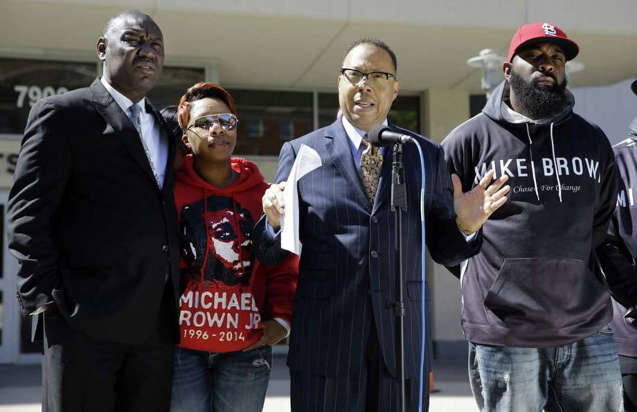 Attorney Anthony D. Gray speaks as Michael Brown's parents, Lesley McSpadden, second from left, and Michael Brown Sr., right, listen along with attorney Benjamin L. Crump, left, during a news conference Thursday, April 23, 2015, in Clayton, Mo. The parents of Michael Brown filed a wrongful-death lawsuit Thursday against the city of Ferguson, Mo., over the fatal shooting of their son by a white police officer, a confrontation that sparked a protest movement across the United States. (AP Photo/Jeff Roberson) Photo: AP / AP