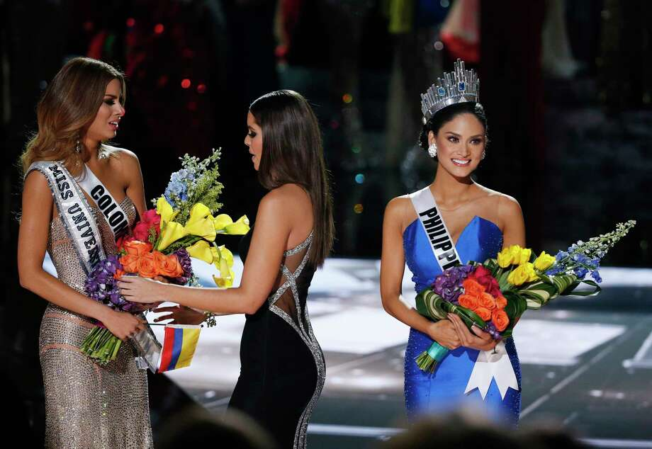 Former Miss Universe Paulina Vega, center, takes away the flowers and sash from Miss Colombia Ariadna Gutierrez, left, before giving it to Miss Philippines Pia Alonzo Wurtzbach, right, at the Miss Universe pageant Sunday in Las Vegas. According to the pageant, a misreading led the announcer to read Miss Colombia Ariadna Gutierrez as the winner before they took it away and gave it to Miss Philippines Photo: Associated Press  / AP
