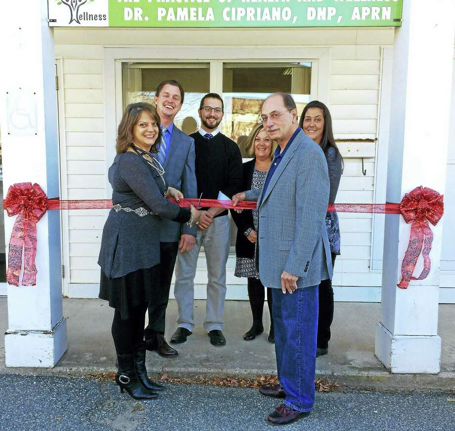 Contributed photohomaston's First Selectman, Ed Mone, assists Dr. Pamela Cipriano as she cuts the Red Ribbon to celebrate the Grand Opening of her new office in Thomaston. They are accompanied by (left to right) Lenny Ollero, Matthew Palasciano, Lucia Rarick and Christine Gary. Photo: Digital First Media