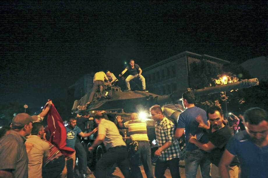 Turkish people attempt to stop a tank moving into position in Ankara, Turkey, late Friday, July 15, 2016. Members of Turkey's armed forces said they had taken control of the country, but Turkish officials said the coup attempt had been repelled early Saturday morning in a night of violence, according to state-run media. Photo: AP Photo — Burhan Ozbilici / Copyright 2016 The Associated Press. All rights reserved. This material may not be published, broadcast, rewritten or redistribu