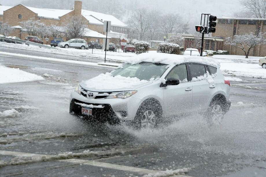 A car splashes through a slush puddle in North Adams, Mass., during a winter storm on Sunday, Nov. 20, 2016. Photo: Gillian Jones/The Berkshire Eagle Via AP  / The Berkshire Eagle