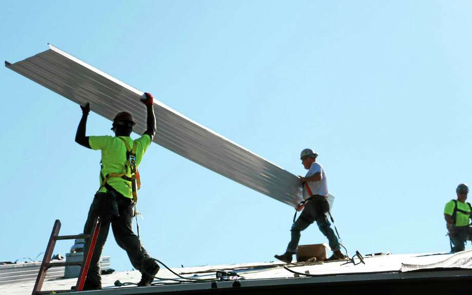 Lamont Foy, Kevin Morin and Pete Willette work on the roof of Barkhamsted Elementary School with contractor Beaulieu Company of Manchester. Photo: John Fitts – The Register Citizen