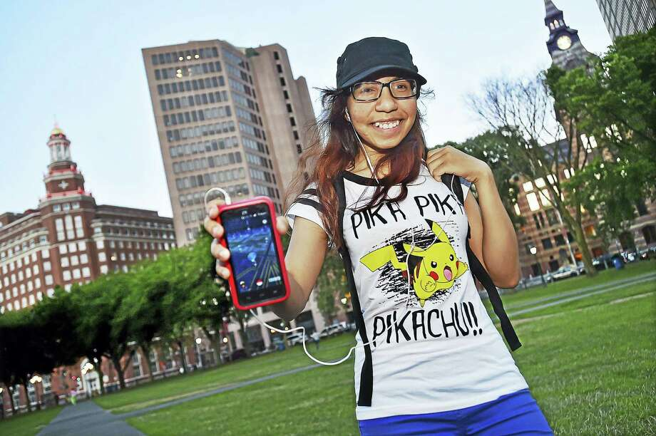 Jenny Calderon, 17, strolls the New Haven Green on Wednesday, wearing her Pikachu shirt and blue pants, indicating she is a member of Team Mystic in search of Pokémon characters using her Android phone. Photo: Catherine Avalone – The Middletown Press  / New Haven RegisterThe Middletown Press
